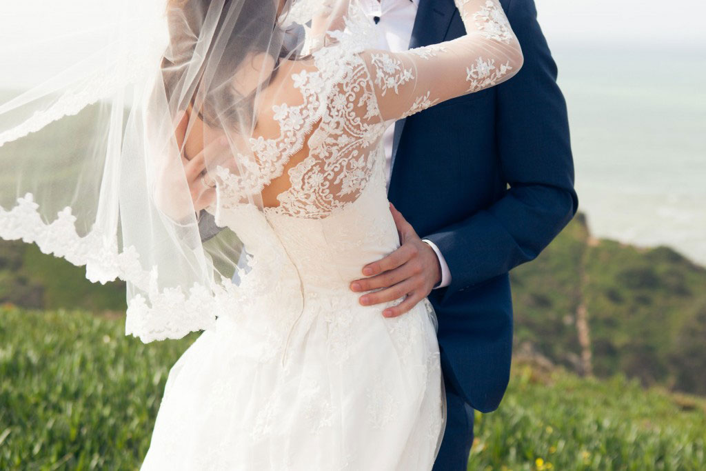 groom kissing bride at an oceanfront venue