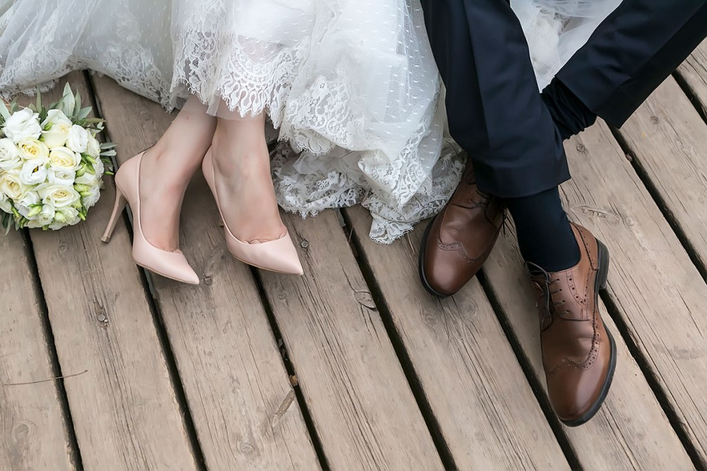 image of a bride's and groom's shoes and the flower bouquet