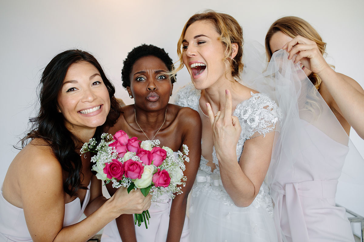 bride and her three bridesmaids taking pictures