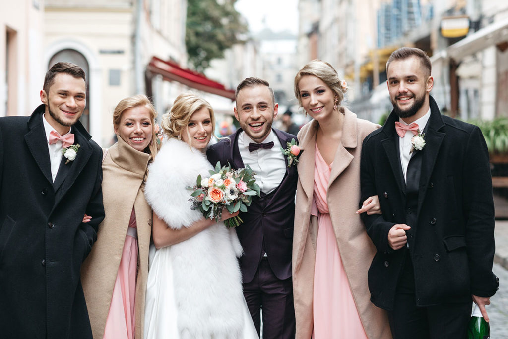 bride, groom, and their two groomsmen and bridesmaids in clothed for a winter wedding downtown charleston