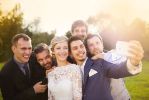 bride and groom taking selfie with guests