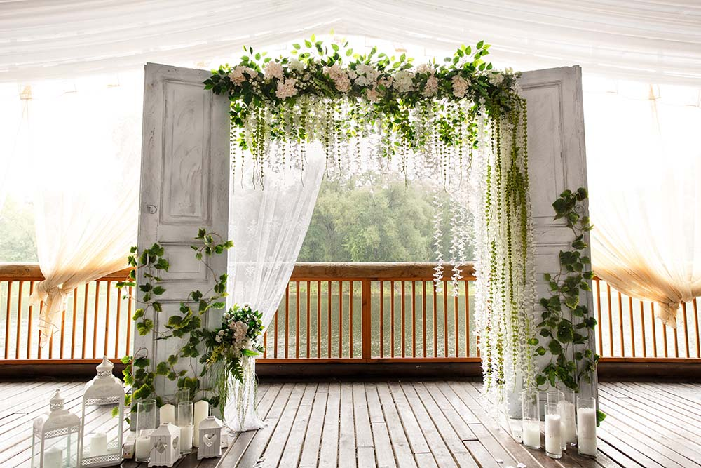 wedding ceremony floral and decorative installation with double doors