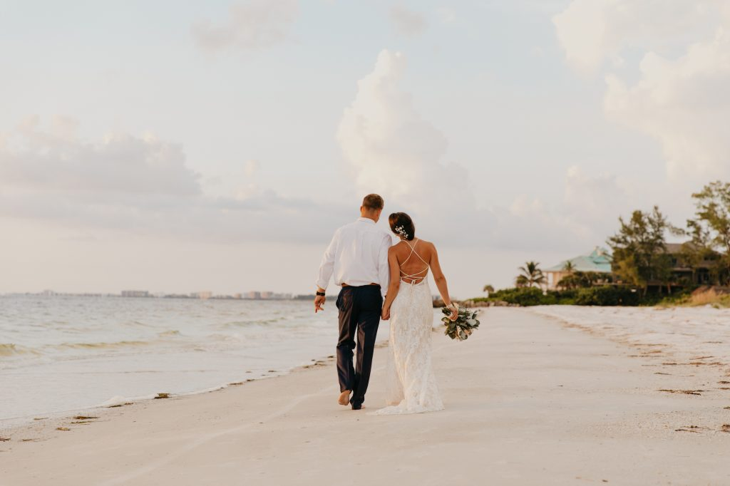 newly married couple walking on Seabrook Island beach