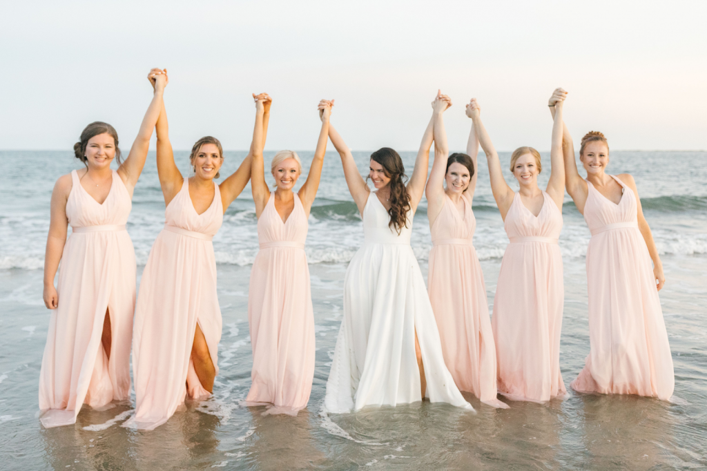 Bridesmaids, dressed in pink, and bride, dressed in white, stand hand in hand in front of the water on the beach